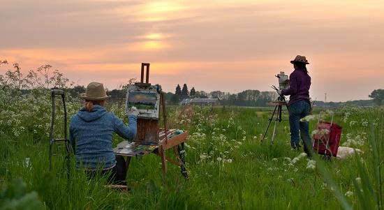 Foto van 2 personen die aan het schilderen zijn in de natuur